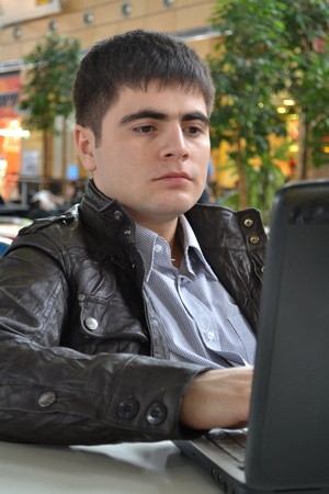 entrepeneur: Casual young man with his laptop  in a cafe Stock Photo