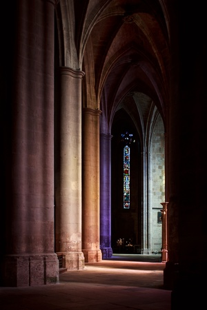 Interior of the ancient gothic cathederal in Southern France. Perspective with stained glass.