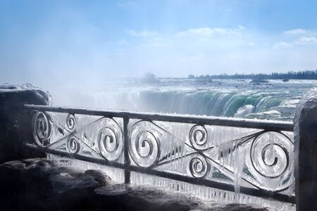 Decorative iron fence covered by thick layer of frozen mist. Niagara Falls on background.