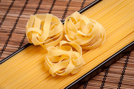 Unboiled tagliatelle and spaghetti on a rural mat