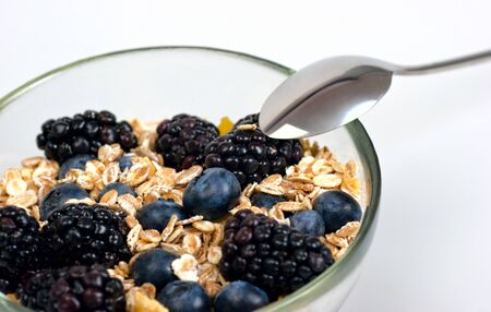 A glass bowl full of muesli, corn flakes, blackberries and blueberries. Selective focus.