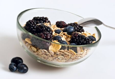 A glass bowl full of muesli, corn flakes, blackberries and blueberries. Selective focus. White background. Banco de Imagens