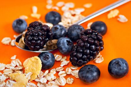 Muesli, corn flakes, blackberries and blueberries on a bright orange backround. Selective focus.