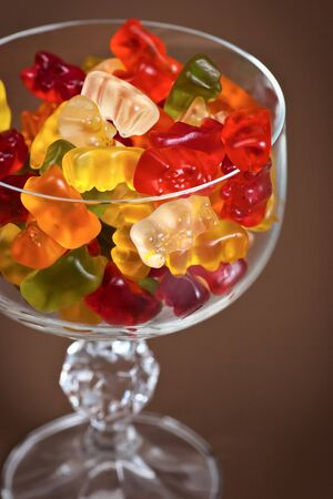 A pile of multicolored gummy bears in a crystal glass on a dark brown background. Selective focus.