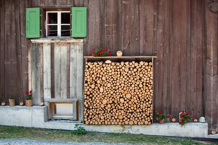 Typical rural house wall with a log rack. Switzerland