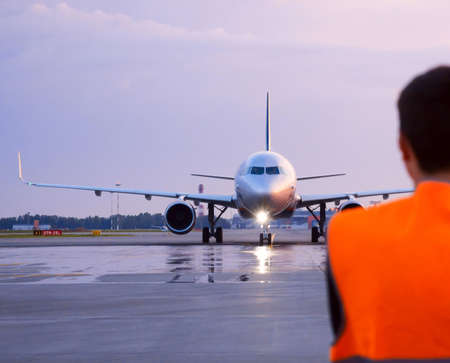 Aircraft maintenance technician in front of Airbus A320 taxiing plane Banco de Imagens
