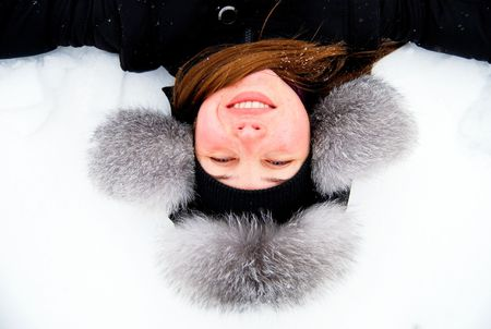 beautiful girl in fur hat lying in the snow upside down photo