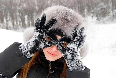 beautiful girl in winter clothing holds her hands like sunglasses