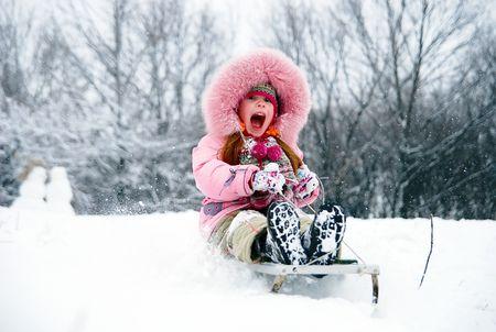 kleine Mädchen im Winterbekleidung sinkt auf Schlitten hinunter den Hügel