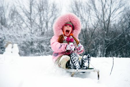 little girl in winter clothing goes down on sleds down the hill Stock Photo