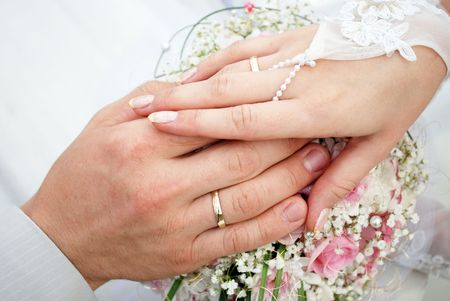Hands of the groom and the bride with wedding rings on top of the brides bouquet Stock Photo