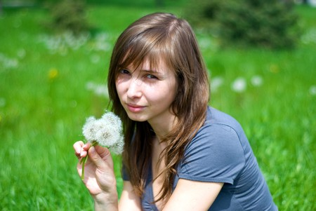 teenage girl on a green meadow with a bouquet of dandelions Stock Photo