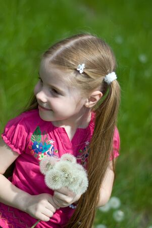 smiling little girl on a green meadow with a bouquet of dandelions