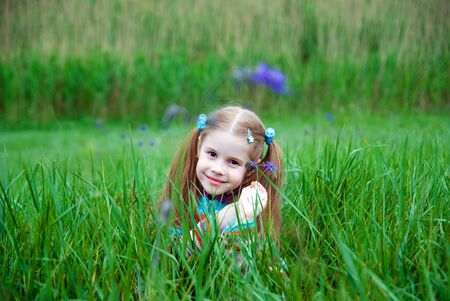 A little girl on a green meadow dressed warmly in a cold summer day