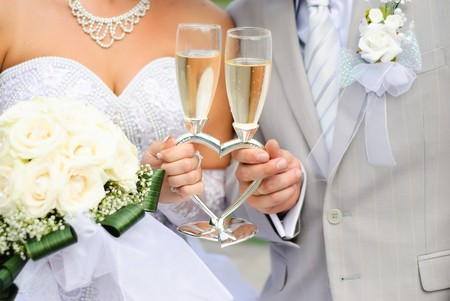 Bride and groom holding wedding heart-shaped glasses with champagne Stock Photo