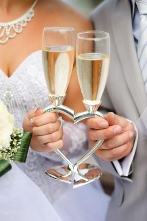 Braut und Bräutigam holding-Hochzeit Heart-shaped Gläser mit Champagner Lizenzfreie Bilder