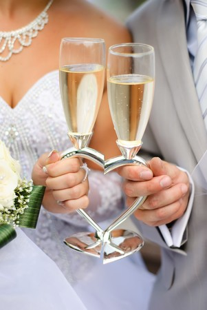 Bride and groom holding wedding heart-shaped glasses with champagne Stock Photo - 8169391