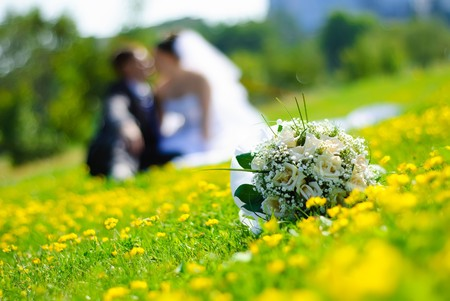 bridal bouquet of white roses on a green meadow and blurred newlyweds