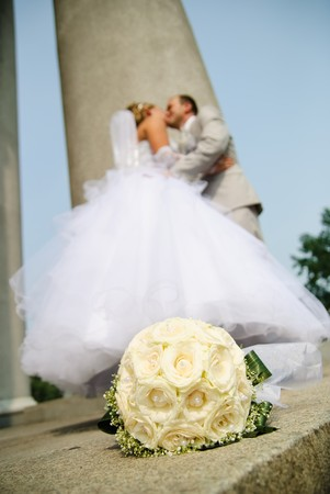 bridal bouquet of white roses and blurred newlyweds at background