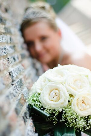 bridal bouquet of white roses and blurred bride near the wall at background Stock Photo