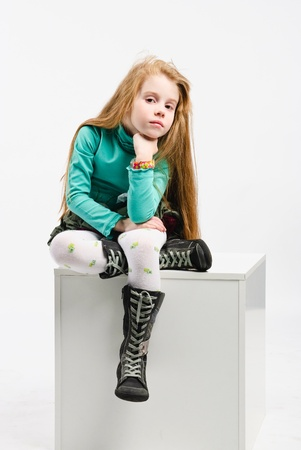 studio shot of pretty little girl sitting on a white cube