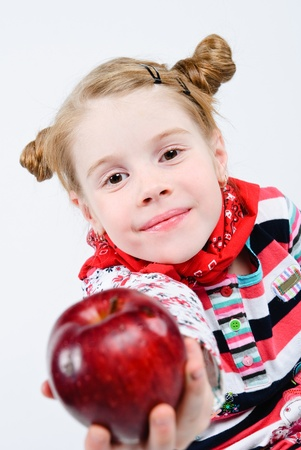 studio shot of pretty little girl offering a red apple