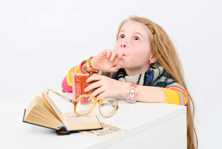 studio shot of pretty little girl reading a book Stock Photo