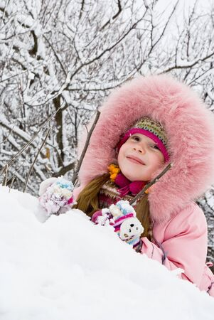 little girl in a winter clothing in a winter woods