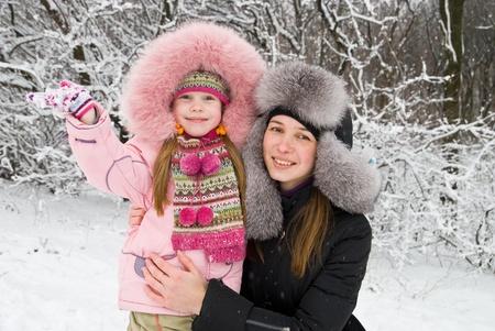 Junge Mutter und Tochter im Winterbekleidung in einem Wald winter