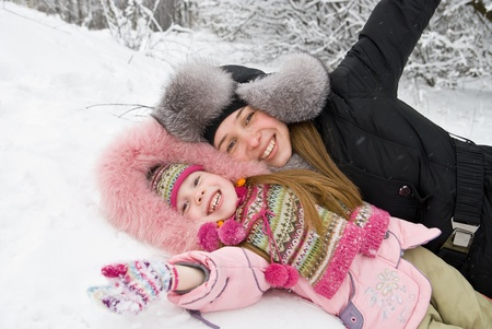 young mother and daughter in winter clothing in a winter woods Stock Photo