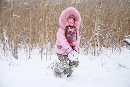 little girl playing with snow in a winter woods Stock Photo