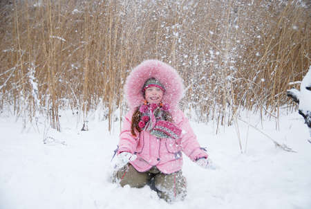 little girl playing with snow in a winter woods photo