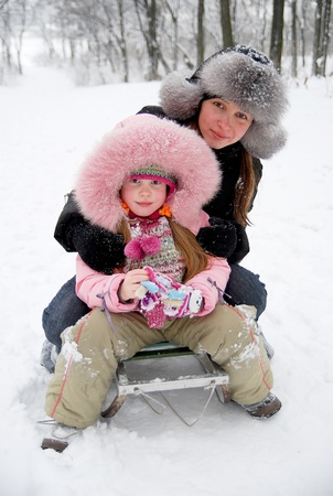 young mother and daugther in winter clothing in a winter woods