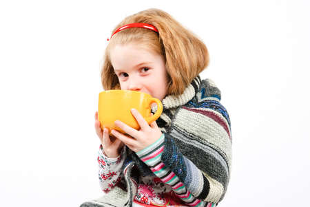studio shot of pretty little girl with a cold holding a cup