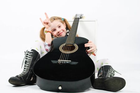 studio shot of pretty little girl playing black acoustic guitar