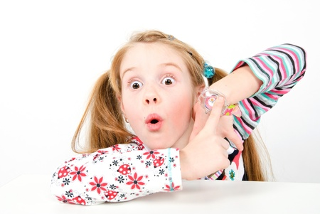 studio shot of pretty little girl pointing at her watch
