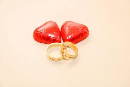 two wedding bands and a heart-shaped candy