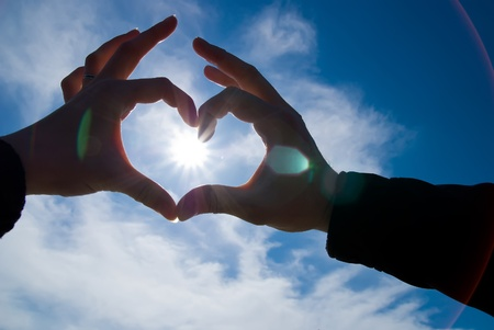 corazon en la mano: dos manos parece coraz�n con sol dentro de Foto de archivo