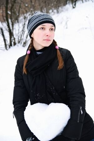 portrait of lovely young woman with heart of snow