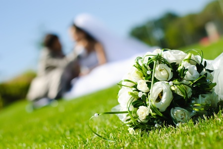 newlywed: bridal bouquet of white roses on a green meadow and blurred newlyweds