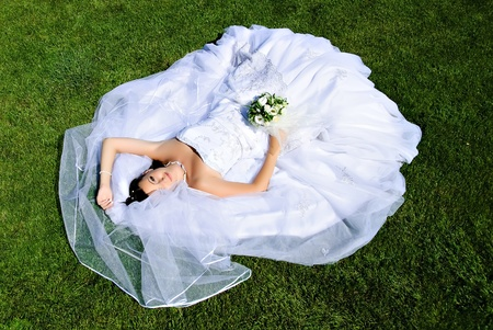 Bride lying on a wedding dress on the grass. Stock Photo