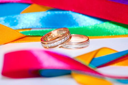 Wedding bands and colorful ribbons. Close-up.