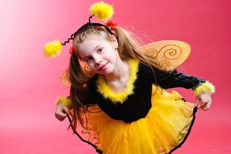 Pretty little girl dressed like a bee. Studio shot. photo