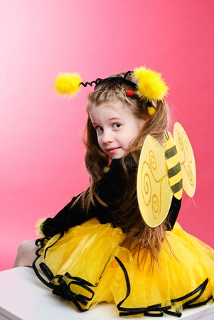 Pretty little girl dressed like a bee. Studio shot.