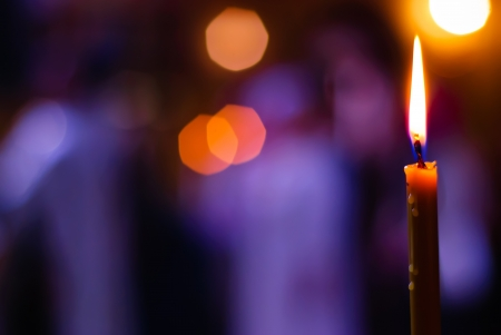 Burning candle on a blurred color background Stock Photo