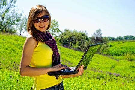 Smiling beautiful woman with laptop outdoor. Sunny summer day.