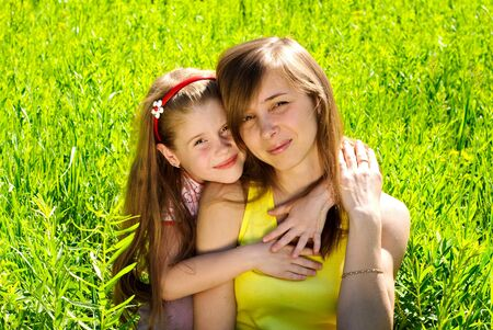 Smiling young mother with little daughter outdoor. Sunny summer day.