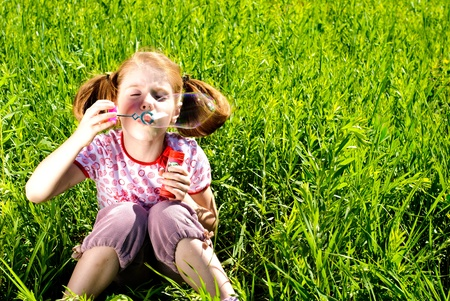 Little girl blowing bubbles on a meadow. Sunny summer day. Stock Photo