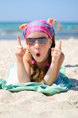 Happy little girl in sunglasses on the beach Stock Photo