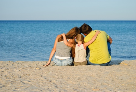 Father, mother and daughter sitting on the beach Stock Photo